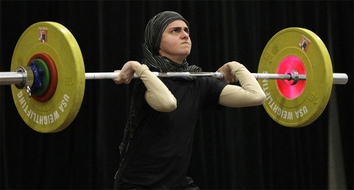 Photo of Arab woman competing during weightlifting championships.